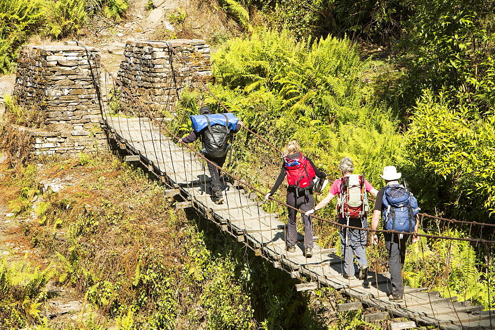 Trekkers crossing a suspension bridge crossing on the Annapurna Base Camp trek, Himalayas, Nepal, Asia